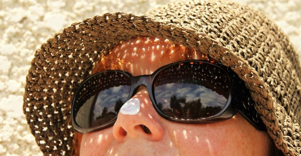 opalająca się dziewczyna w okularach przeciwsłonecznych z kremem na nosie