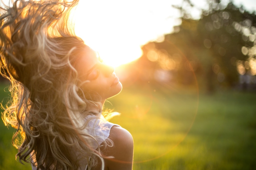 kobieta z bujnymi włosami w promieniach słońca