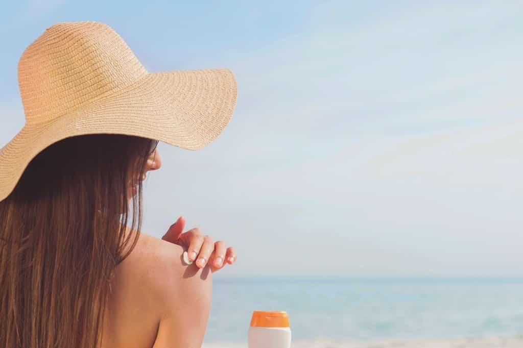 dziewczyna smarująca się kremem na plaży