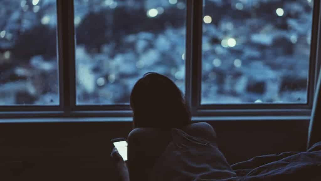 dziewczyna w ciemności wpatruje się w smartfon