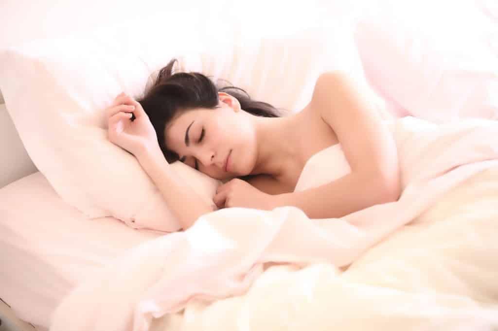 kobieta śpiąca w łóżku na prawym boku